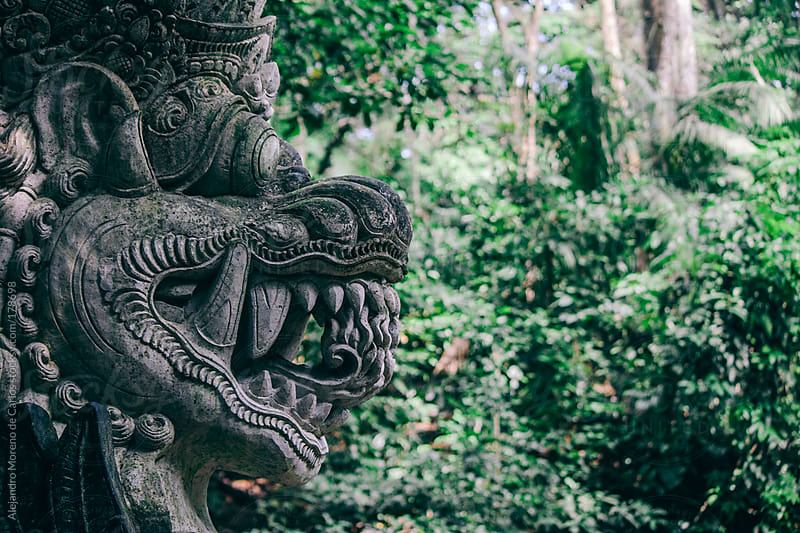 Dragon face statue against green background in Bali, Asia by Alejandro Moreno de Carlos for Stocksy United