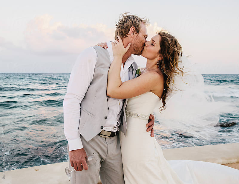 Newlyweds kissing next to the ocean by Shaun Robinson for Stocksy United