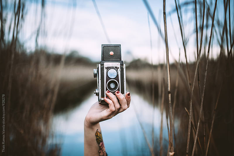 holding a camera in a marsh by Thais Ramos Varela for Stocksy United