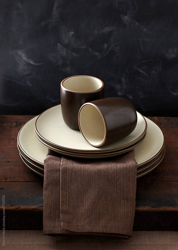 Heathware ceramic plates and cups stacked on wood surface by Sherry Heck for Stocksy United