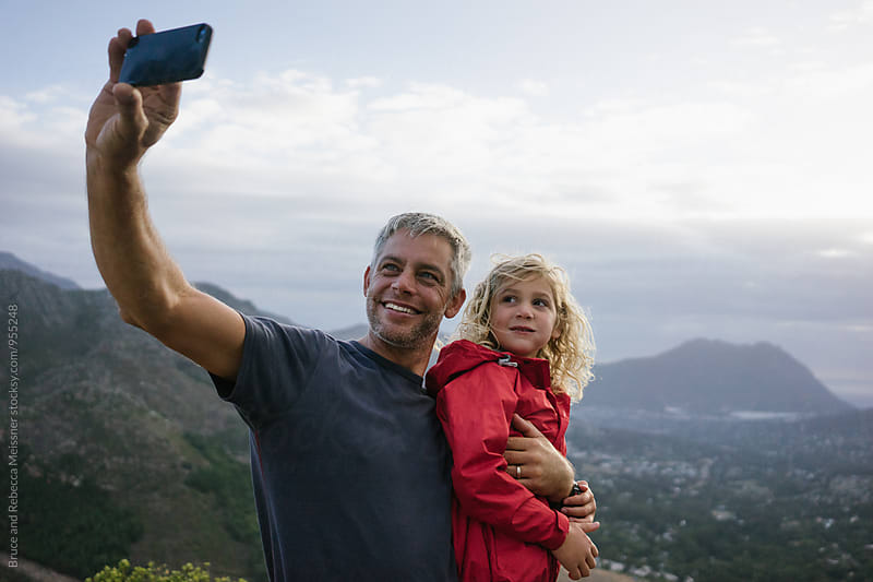 Father and daughter selfie by Bruce and Rebecca Meissner for Stocksy United