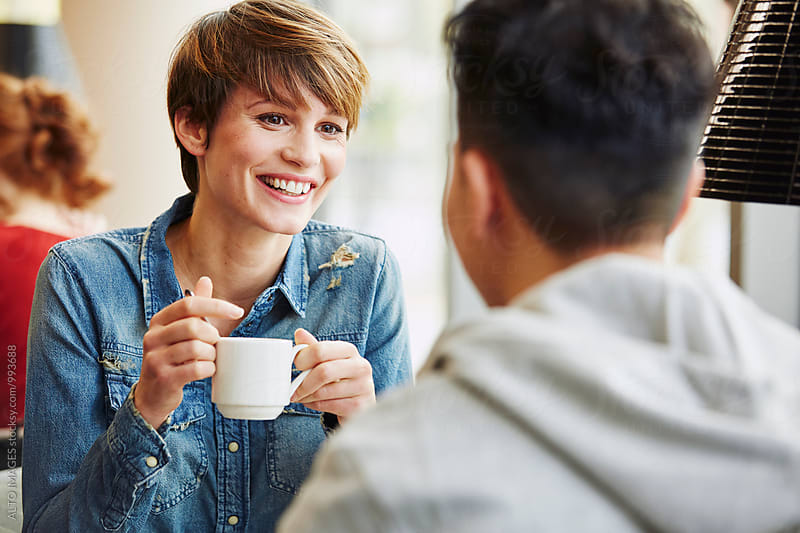 Woman Having Coffee While Talking With Man In Restaurant by ALTO IMAGES for Stocksy United