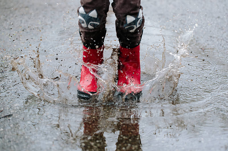 red boots splashing in rain puddle by Brian Powell for Stocksy United