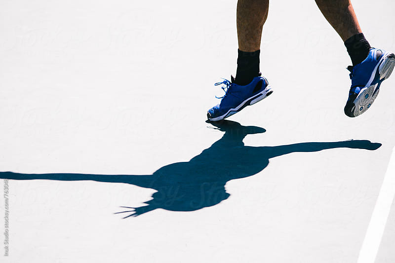 Detail of feet and shadow of a tennis player playing a match in a tennis court by Inuk Studio for Stocksy United