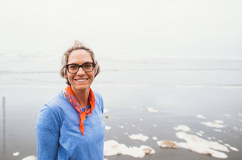 Girl with Glasses Smiling on the Beach by michelle edmonds for Stocksy United