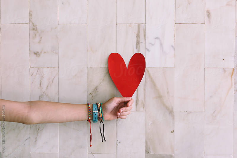 Young teen girl holding a red paper heart in front of a tiled wall by Jacqui Miller for Stocksy United