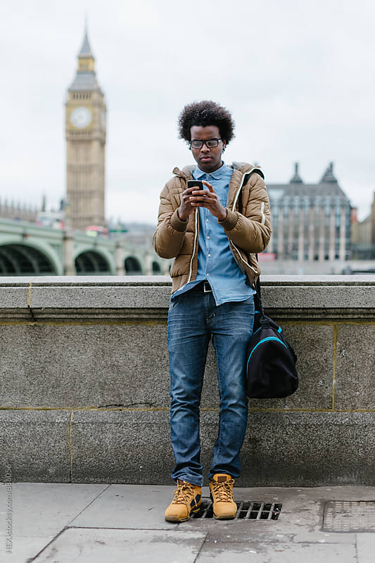 Young Black Commuter with Mobile Phone in London by HEX. for Stocksy United