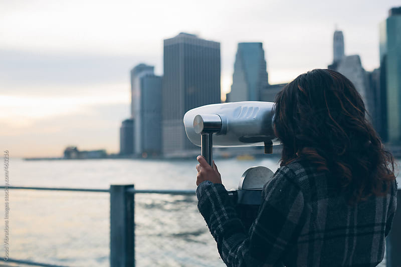 Woman using binoculars in New York City by Good Vibrations Images for Stocksy United