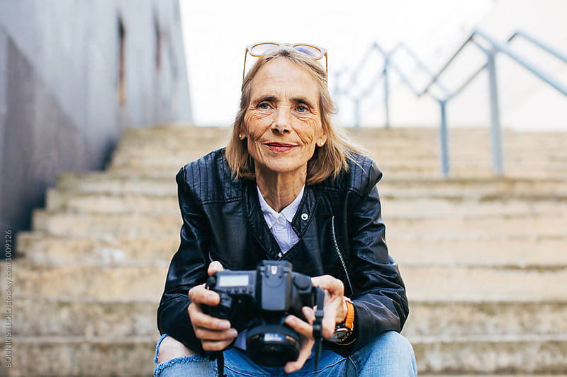 Senior woman holding her camera sitting on stairs.  by BONNINSTUDIO for Stocksy United