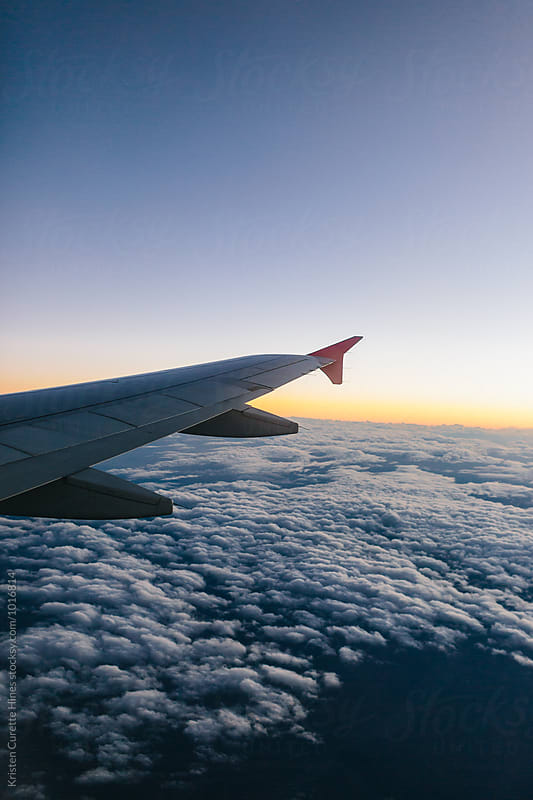 View from an airplane window at dusk  by Kristen Curette Hines for Stocksy United