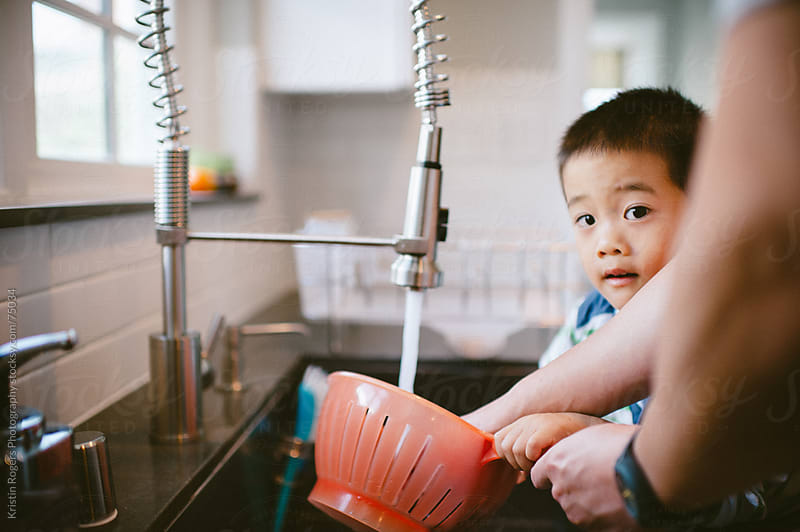 Father helping son wash berries in kitchen sink by Kristin Rogers Photography for Stocksy United