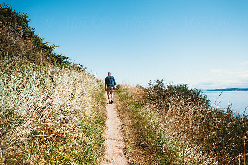 Hiker on an Island Trail in Washington by michelle edmonds for Stocksy United