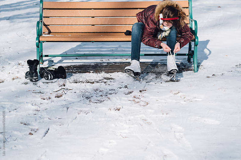 young woman lacing her skates, sitting on  bench, outside. by Léa Jones for Stocksy United