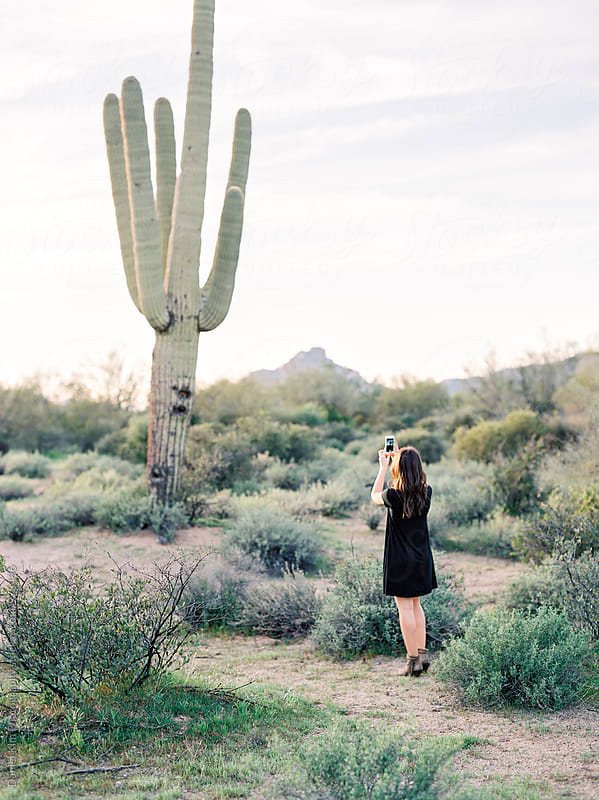 Girl taking photo of cactus by Daniel Kim Photography for Stocksy United