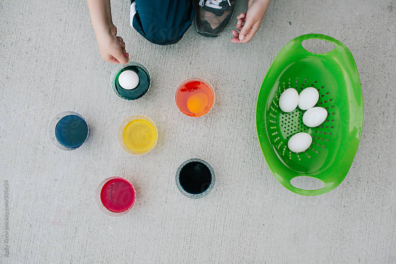 child dipping eggs in dye by Kelly Knox for Stocksy United