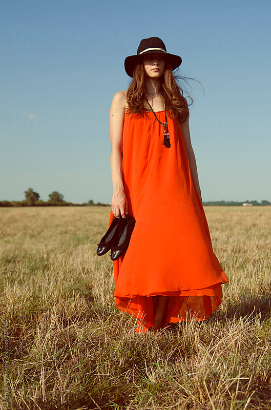 Girl in red dress jumping on the sunny meadow by Marija Anicic for Stocksy United