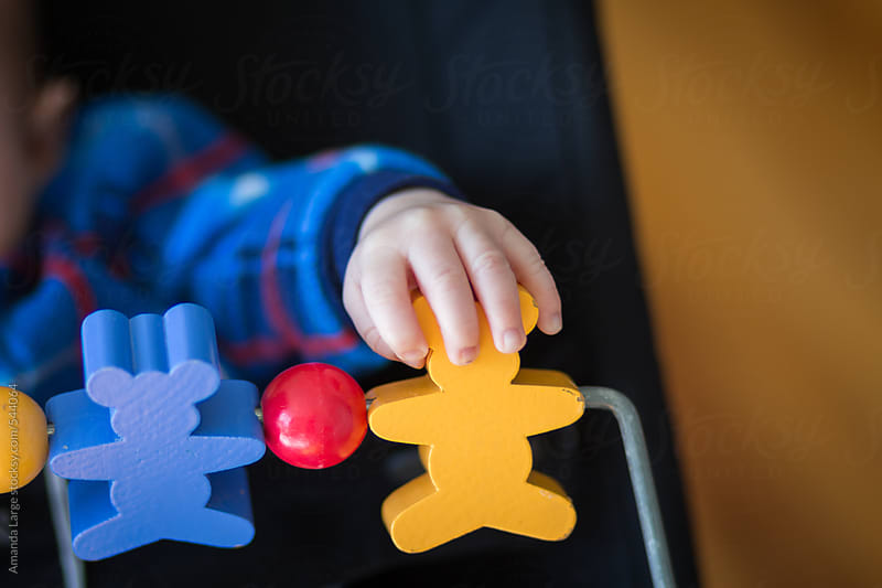 Baby's hand grabbing a wooden toy by Amanda Large for Stocksy United