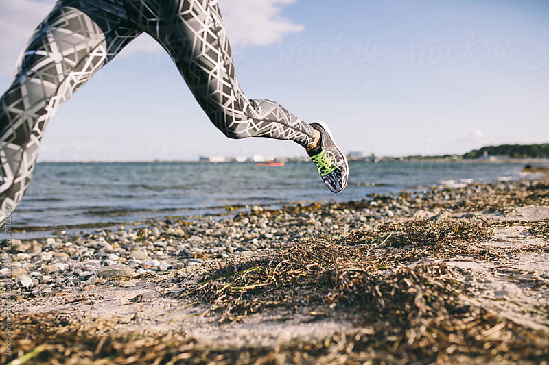 Photograph of running legs on a beach by Jacob Ammentorp Lund for Stocksy United