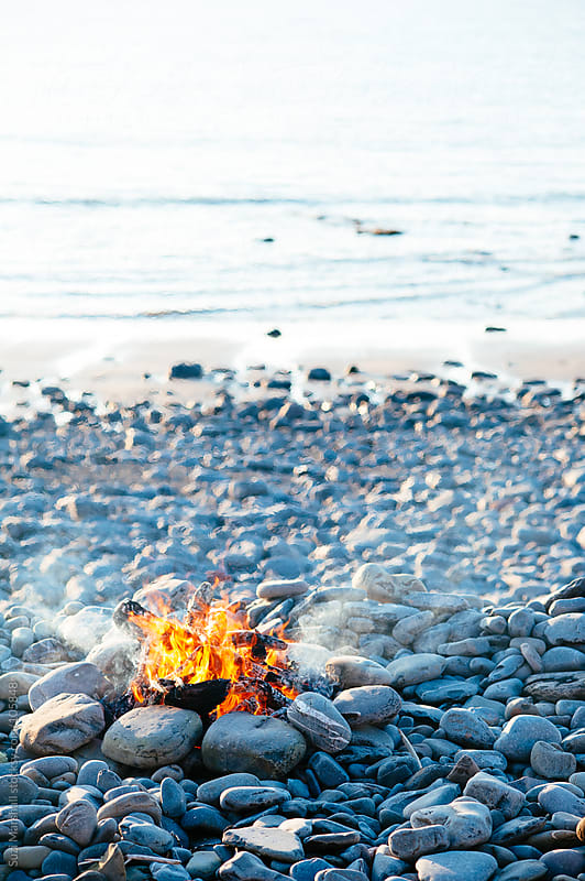 Fire burning on a beach by Suzi Marshall for Stocksy United