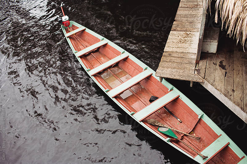 Canoe moored to lodge's dock by Gabriel Tichy for Stocksy United