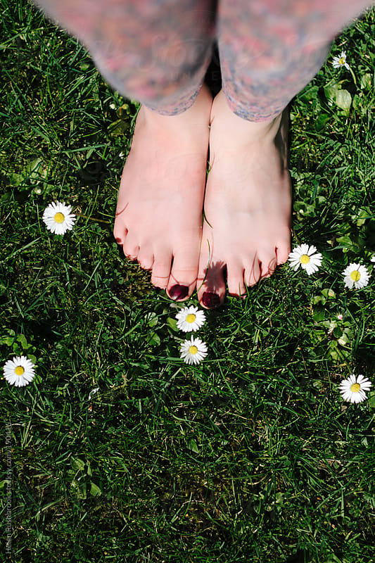 Barefoot among the daisies by Helen Rushbrook for Stocksy United
