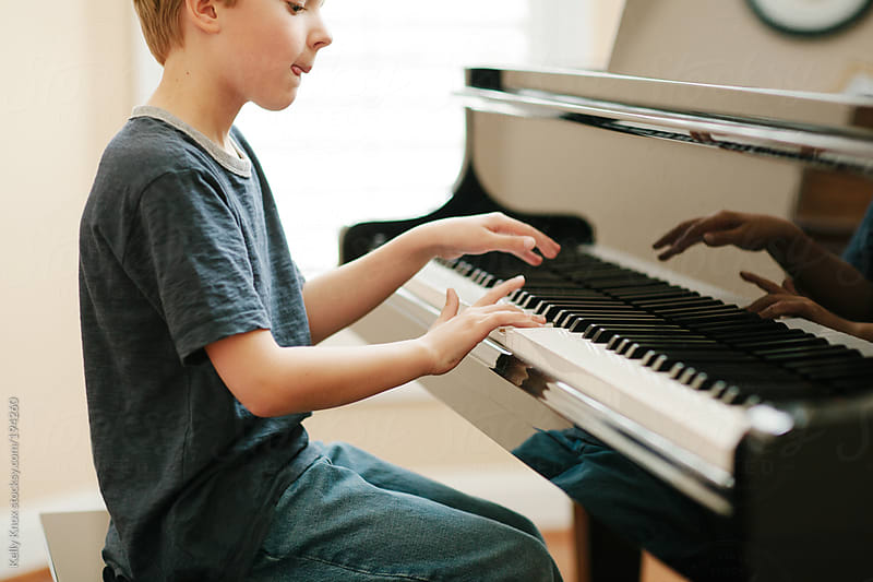 child playing piano by Kelly Knox for Stocksy United