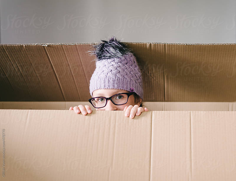 child playing in an empty cardboard box by Gillian Vann for Stocksy United
