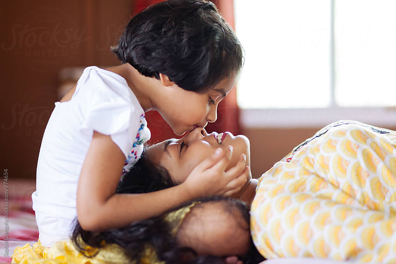 Daughter kissing her mother on her nose by Saptak Ganguly for Stocksy United