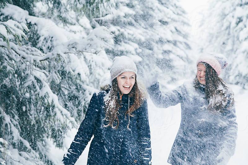Female couple enjoying snowball fight by Borislav Zhuykov for Stocksy United