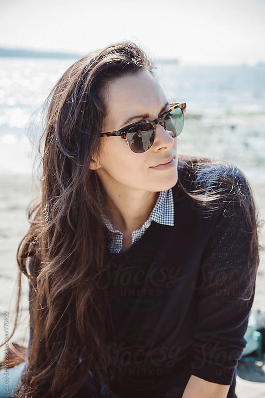 Portrait of stylish woman wearing sunglasses on a beach by Carey Shaw for Stocksy United