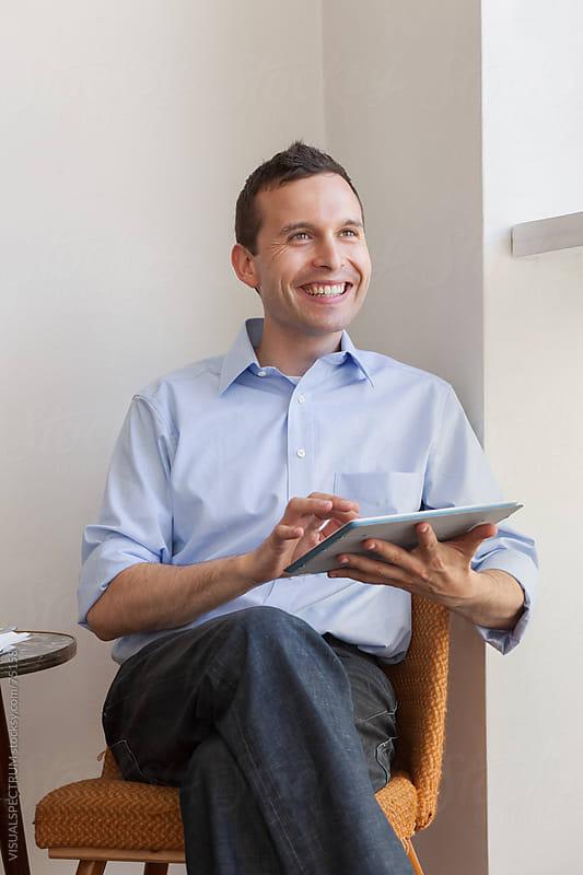 Smiling Man With Digital Tablet by Julien L. Balmer for Stocksy United
