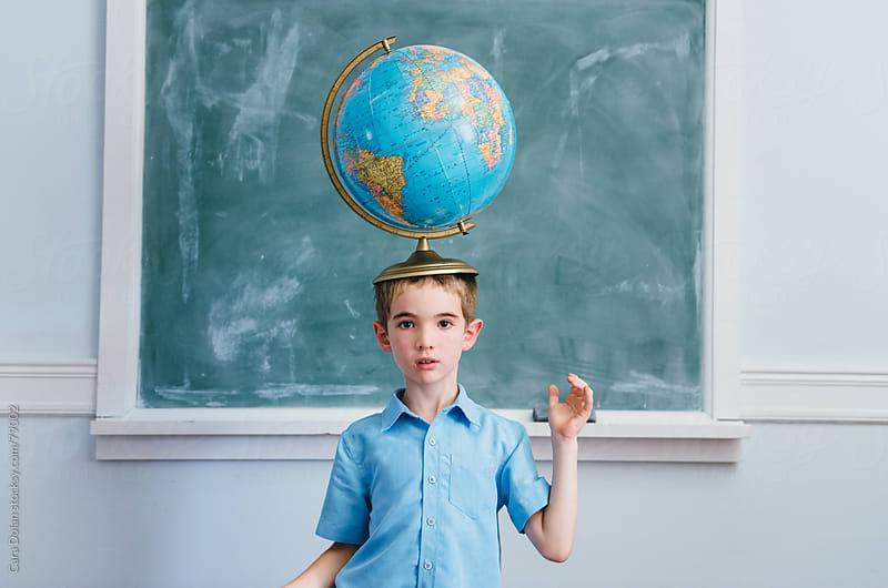 Boy in a classroom balances a globe on his head by Cara Dolan for Stocksy United