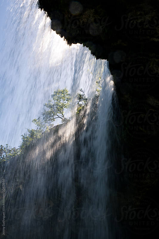 Behind waterfall with light rays by Jenny Sathngam for Stocksy United