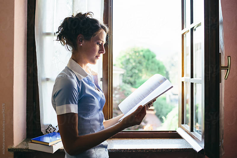 Girl studying at the window. by michela ravasio for Stocksy United