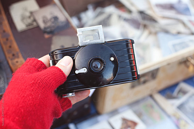 hand holding an old cameras for sale at a flea market by Natalie JEFFCOTT for Stocksy United