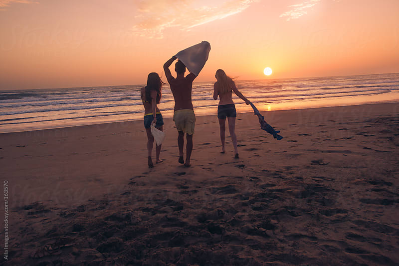 Friends on the beach about to swim in the sea at Sunrise by Aila Images for Stocksy United