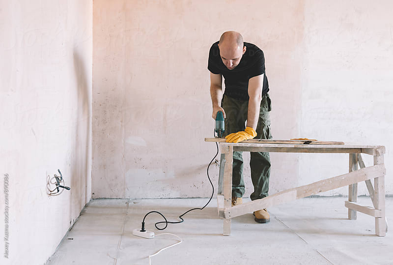 man cutting wood plank with a saw by Alexey Kuzma for Stocksy United