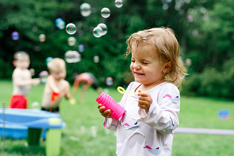 Young girl blowing bubbles outside by Maria Manco for Stocksy United