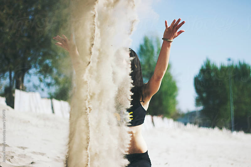 Young woman throwing sand in the air by Jovana Rikalo for Stocksy United