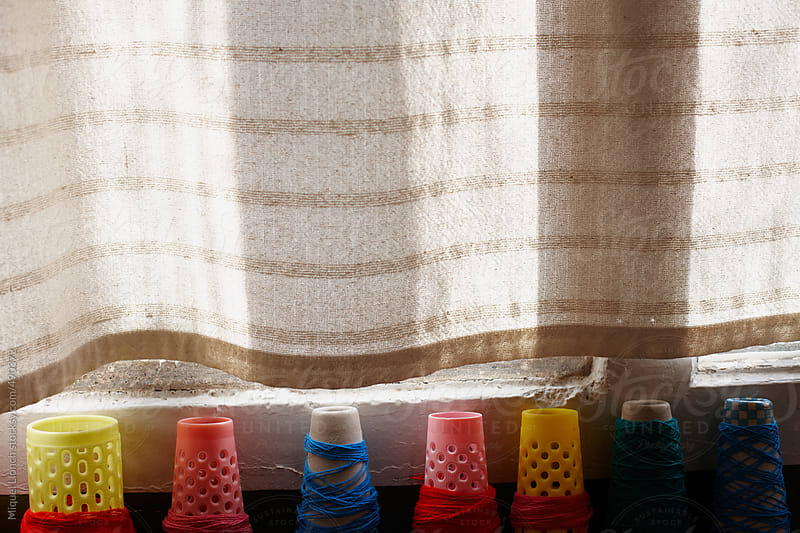 Close up of colorful thread cones in front of a window by Miquel Llonch for Stocksy United