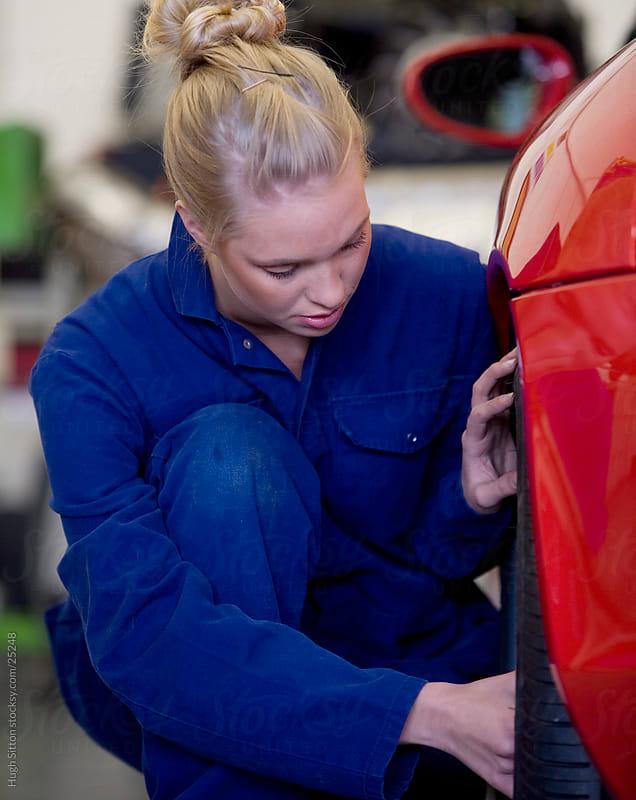 Female car mechanic working in busy garage. by Hugh Sitton for Stocksy United