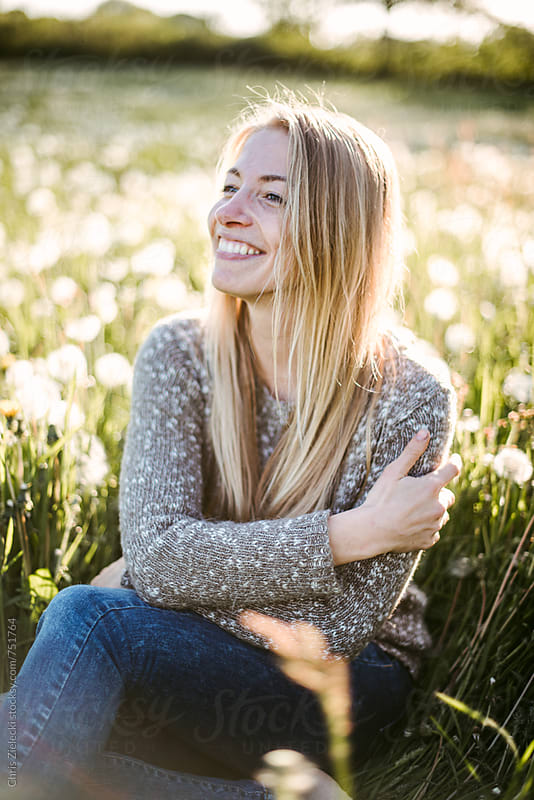 a girl is sitting in a dandelion meadow by Christian Zielecki for Stocksy United