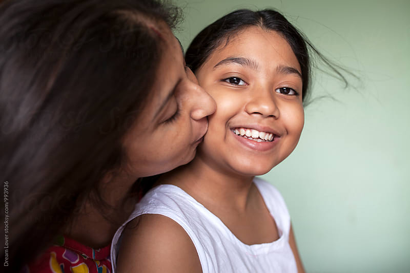 Mother kisses her daughter by PARTHA PAL for Stocksy United