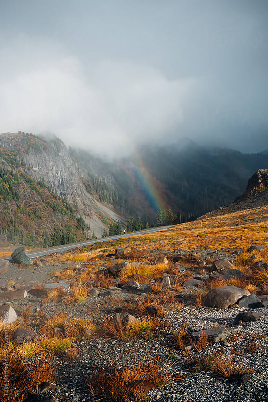 Rainbow And Dark Clouds Over Rocky Mountainside by Luke Mattson for Stocksy United