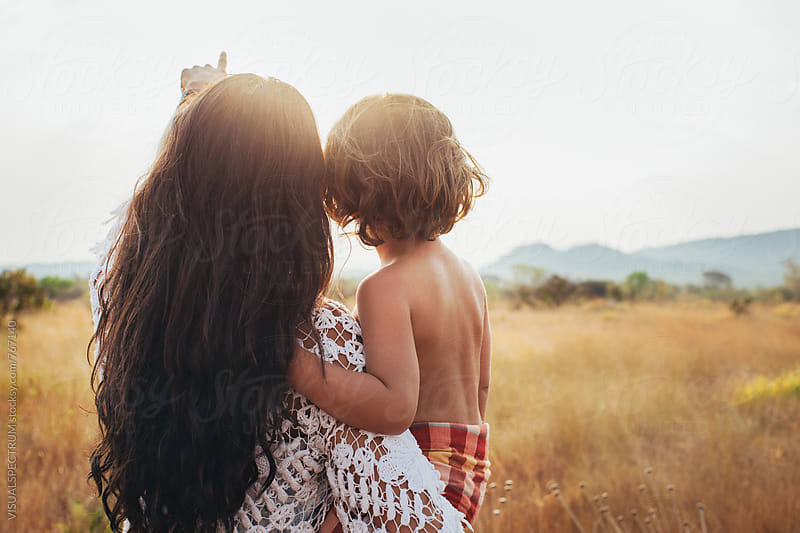 Mother and Child - Pretty Brunette Holding Cute Young Boy and Pointing at Sun by VISUALSPECTRUM for Stocksy United
