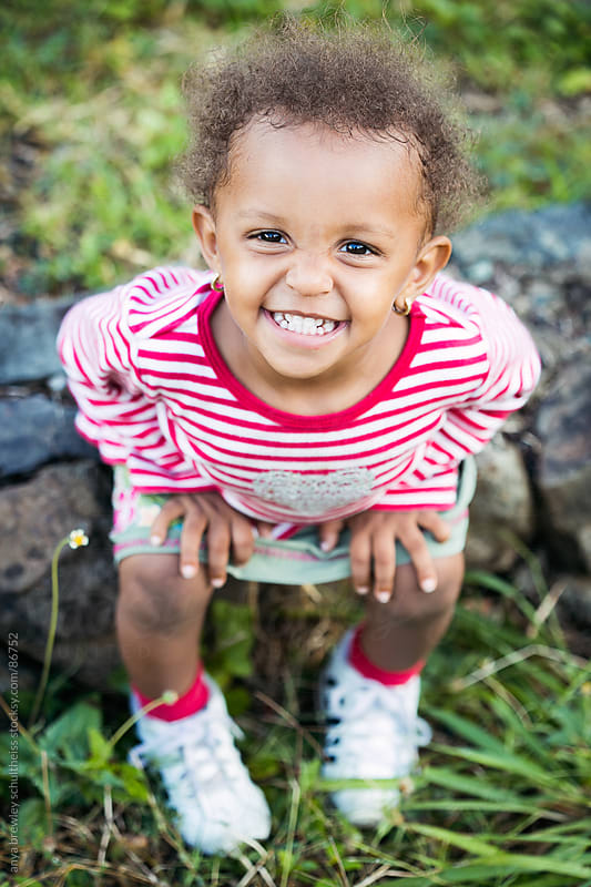 Portrait of toddler girl smiling happily by anya brewley schultheiss for Stocksy United