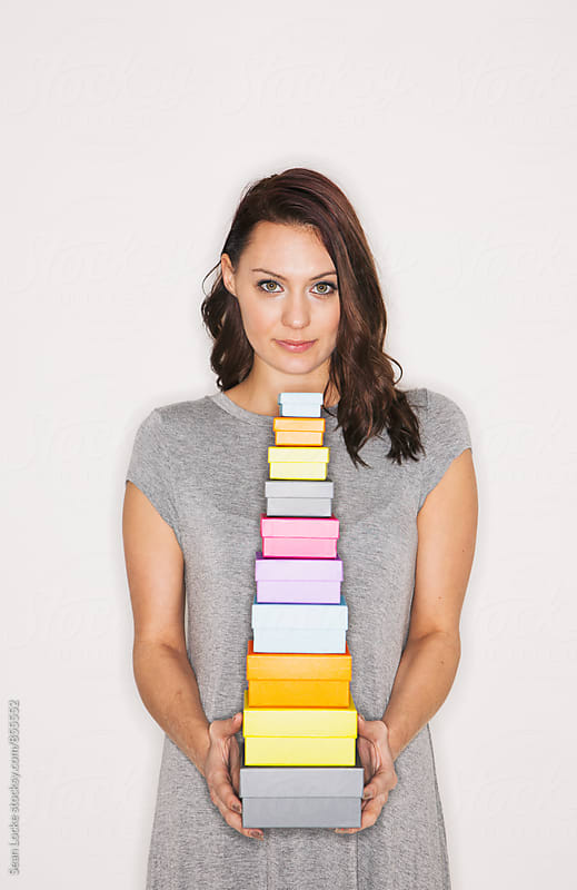 Woman Holding Stack Of Boxes by Sean Locke for Stocksy United