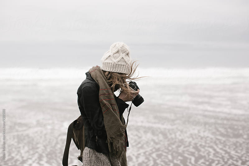 young woman taking photos at beach on cloudy day by Nicole Mason for Stocksy United