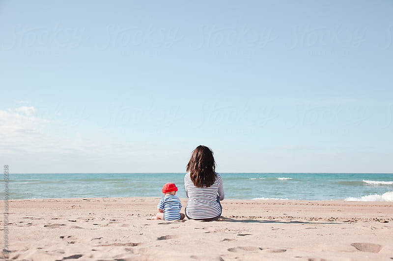 Mom with her baby sitting backward on the beach by BONNINSTUDIO for Stocksy United