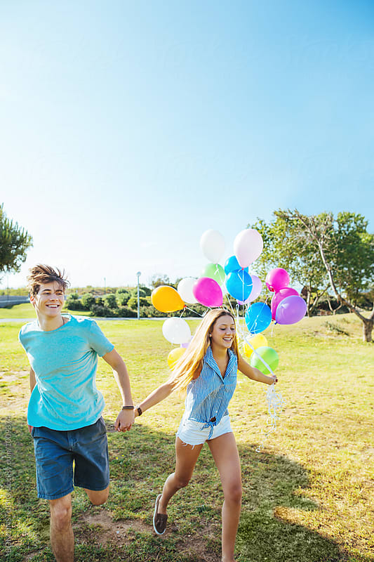 Teenage couple holding colorful balloons having fun in a park. by BONNINSTUDIO for Stocksy United